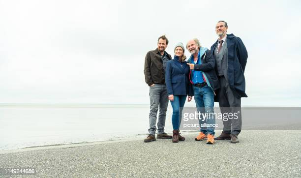 June 2019, Lower Saxony, Norddeich: Kai Maertens , Julia Jentsch and Christian Erdmann sit on the dike during the press date for the Saturday...