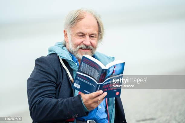 KlausPeter Wolf sits on the dike and looks into his book The fourth film in the Ostfriesland crime series is based on the novel of the same name by...