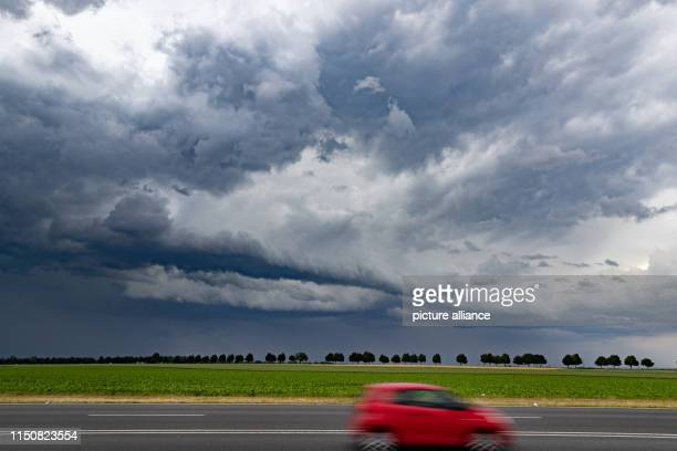 June 2019, North Rhine-Westphalia, Bergheim: A red car is driving on a federal highway. In the background dark thunderclouds can be seen. Photo:...
