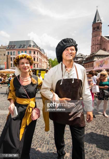 June 2019, Rhineland-Palatinate, Mainz: Volker Hans, as Johannes Gensfleisch, called Gutenberg, and Leopoldine Chazeaud, as Frau von Gutenberg, walk...