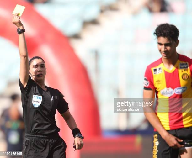Dorsaf Ganoiati raises a yellow card during the Tunisian Ligue Professionnelle 1 soccer match between Esperance Tunis and CA Bizertin at Stade El...