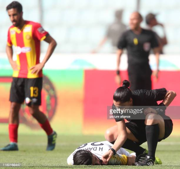 Dorsaf Ganoiati speaks to a player lays on the ground as she runs a Tunisian Ligue Professionnelle 1 soccer match between Esperance Tunis and CA...