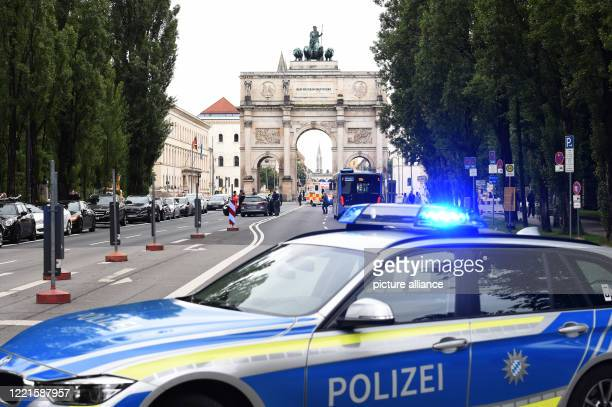 June 2020, Bavaria, Munich: An ambulance is standing at a car that lost control while driving and caused an accident, is standing in front of the...