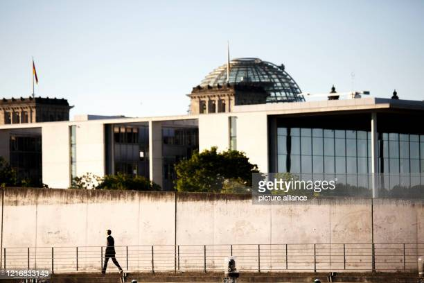 Man walks along the banks of the Spree past the Marie- Elisabeth-Lüders-Haus with the Reichstag building in the background. Photo: Carsten Koall/dpa