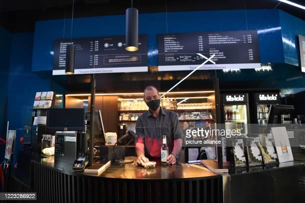 Ronald Graeber, theatre director of the Delphi Lux cinema in Berlin-Charlottenburg, passes snacks and a bottle of water through a Plexiglas panel in...