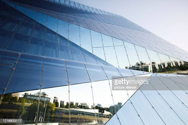 """The Reichstag building is reflected in the façade of the """"Cube Berlin"""" office building at the main railway station. Photo: Carsten Koall/dpa"""