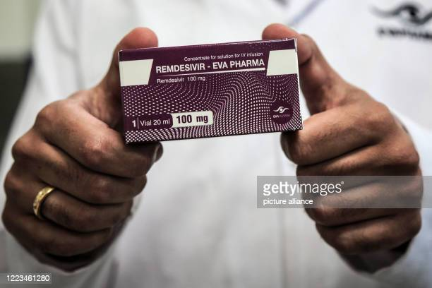 June 2020, Egypt, Giza: An employee of Egyptian pharmaceutical company Eva Pharma holds a pack containing vials of Remdesivir, a broad-spectrum...