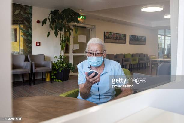 June 2020, Hessen, Kassel: Resident Jenny Nelle talks to a visitor via a baby monitor and through a Plexiglas panel in the entrance area of the AWO...