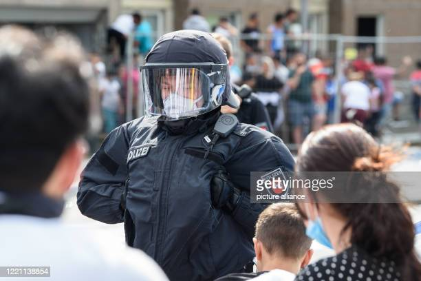 June 2020, Lower Saxony, Göttingen: A policeman is standing in front of a group that is standing in front of the quarantined residential building in...