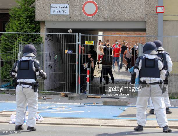 June 2020, Lower Saxony, Göttingen: A stone is thrown at police officers standing in front of the residential complex on Groner Landstrasse, which is...