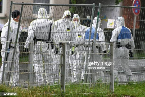 June 2020, Lower Saxony, Göttingen: Cops in protective gear are standing outside an apartment building on a cordoned area. With about 100 new...