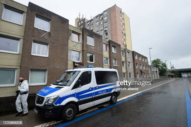 June 2020, Lower Saxony, Göttingen: Police officers in protective gear are standing outside a residential building. In view of about 100 new...