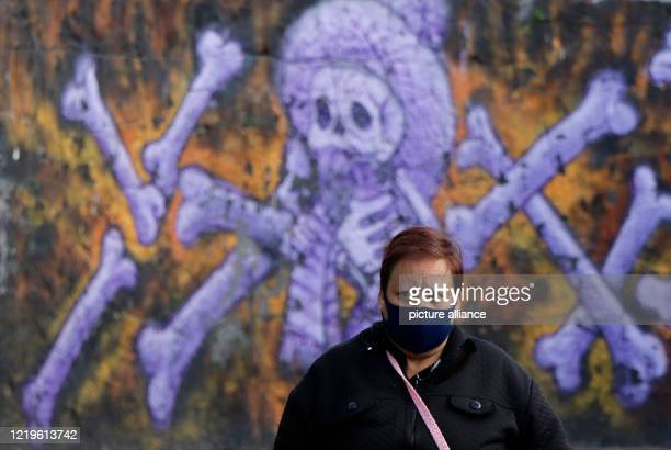 A woman wearing a black face mask stands at the entrance of the crematorium San Nicolas Tolentino in front of a mural in the middle of the Corona...