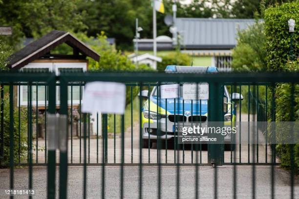 June 2020, North Rhine-Westphalia, Münster: A police car is parked behind a gate of an allotment colony. An arbour in the colony is one of the crime...