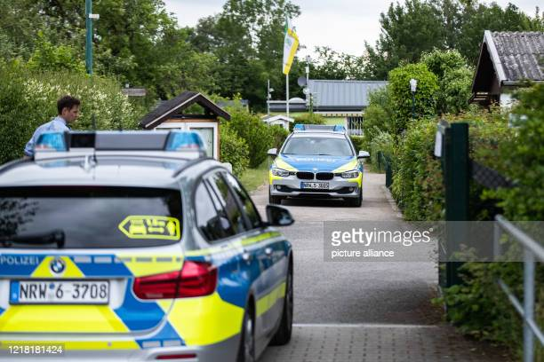 June 2020, North Rhine-Westphalia, Münster: Two police cars are parked in the driveway of an allotment garden colony. An arbour in the colony is one...