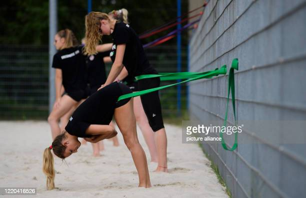 Lenka Dürr player at the women's volleyball Bundesliga club Dresdner SC trains during an athletic unit on the beach volleyball court with an elastic...