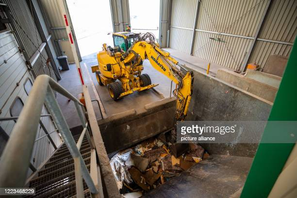June 2020, Saxony, Kleincotta: An excavator takes the bulky waste to the Kleincotta recycling centre near Pirna. Here the waste is not separated and...