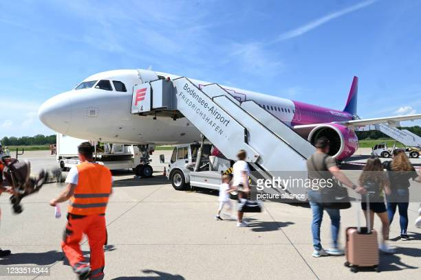 June 2021, Baden-Wuerttemberg, Friedrichshafen: Passengers walk with luggage to the plane to Skopje in northern Macedonia at Lake Constance Airport....