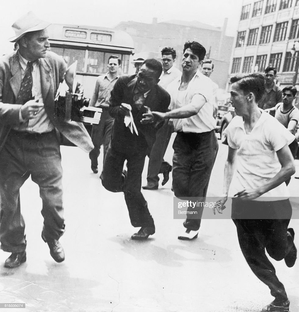 This negro, center, has just been slugged by young white hoodlums, in Detroit's race riot and is frantically trying to escape before they hit him again.