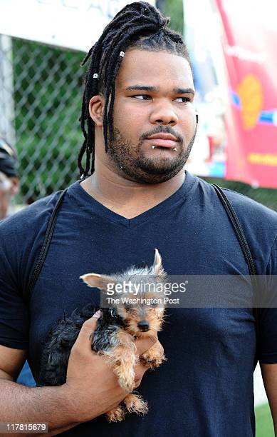 Antonio Logan of Washington DC with his nine week old yorkie Remy watch the basketball action of the Goodman League summer basketball tournament at...