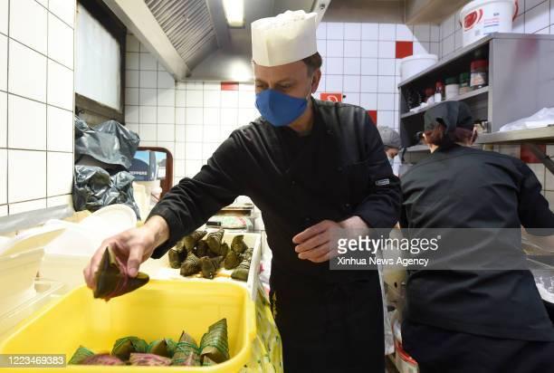 June 23, 2020 -- Spaghetti chef Suman L puts Zongzi into a box at restaurant Pizzeria Don Giovanni in Vienna, Austria, June 23, 2020. Zongzi is a...