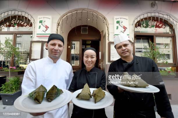 June 23, 2020 -- Wu bing C, spaghetti chef Suman R and pizza chef Nuri show Zongzi at the restaurant Pizzeria Don Giovanni in Vienna, Austria, June...