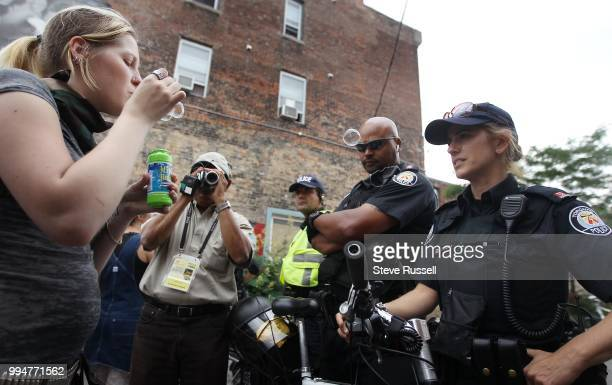 Courtney Winkels blows bubbles much to the consternation of Officer Adam Josephs sunglasses who threatens to arrest her for assault People protest at...