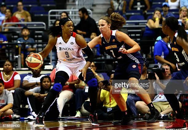 Kia Vaughn of the Washington Mystics shields the ball from Kayla Pedersen of the Connecticut Sun during a WNBA game at Verizon Center in Washington...