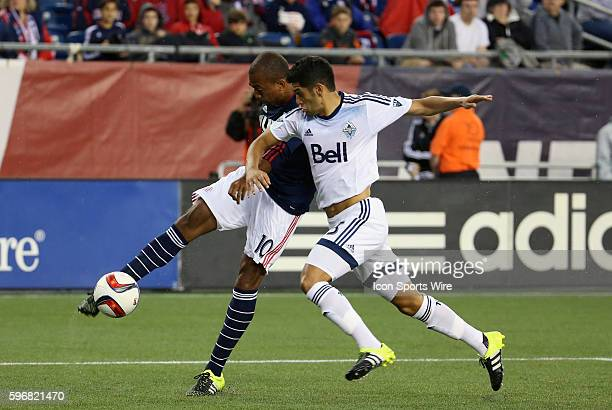 New England Revolution midfielder Teal Bunbury gets the cross in with Vancouver Whitecaps midfielder Matias Laba closing in The Vancouver Whitecaps...