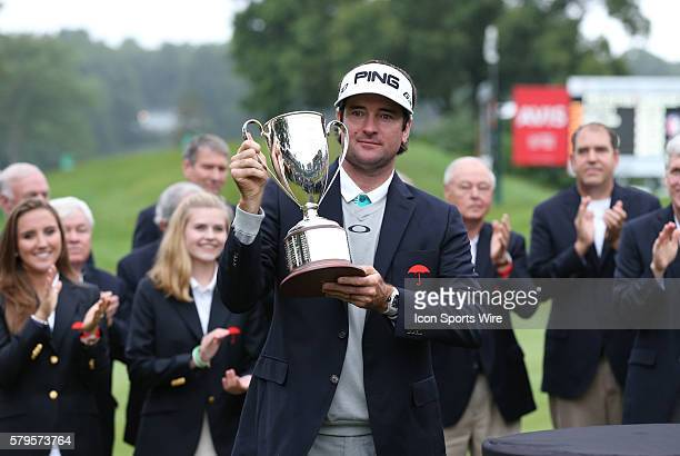Bubba Watson hoists the trophy after winning the Traveler's Championship at TPC River Highlands in Cromwell Connecticut