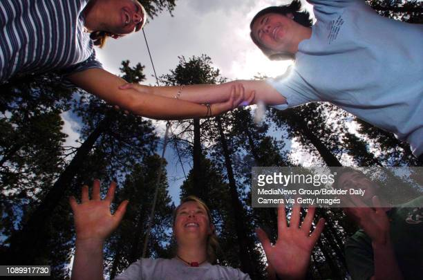 June 4 2004 / Allenspark CO / Sara DeWaay left of Atlanta GA and Lizzie Buchanan right balance agaist each other during a confidence course excise...