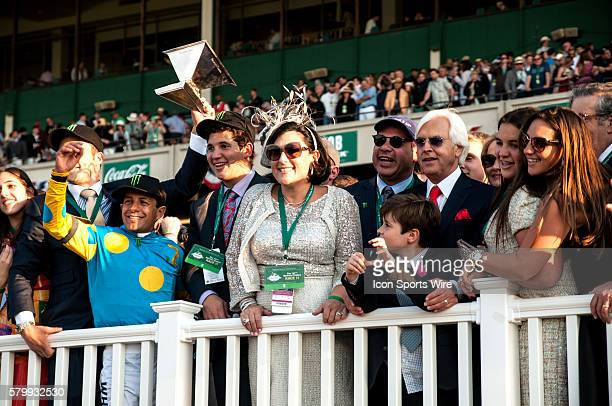 Jockey Victor Espinoza holds up the Triple Crown Trophy as he poses with Hall of Fame trainer Bob Baffert and Baffert's family and associates after...