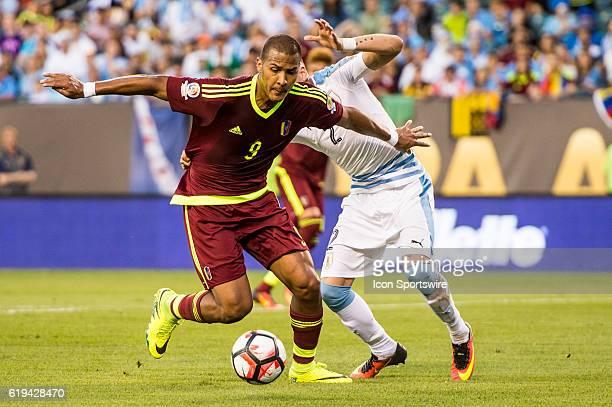 Venezuela forward Jose Salomon Rondon makes a move around Uruguay defender Jose Gimenez during the 1st half of the match between Uruguay versus...