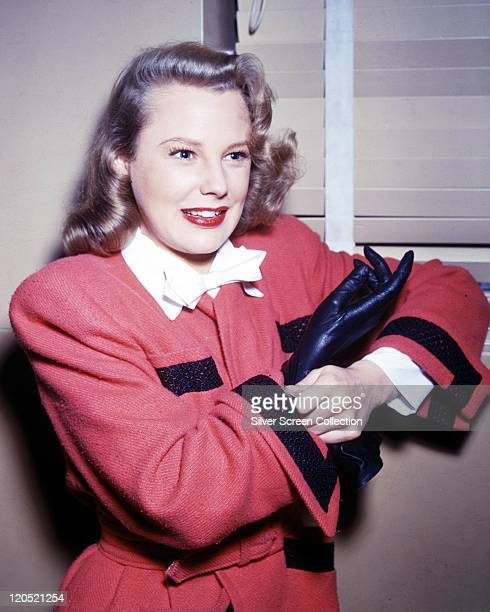 June Allyson US actress putting on a black leather glove wearing a red coat with black trim circa 1945