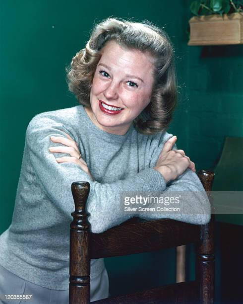 June Allyson US actress smiling wearing a grey woollen jumper leaning on the back of a chair in a studio portrait against a green background circa...