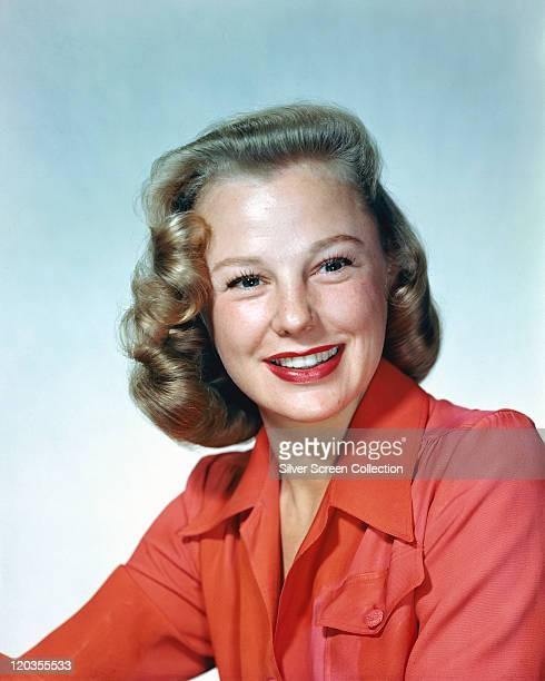 June Allyson US actress smiling wearing a red blouse in a studio portrait against a white background circa 1950