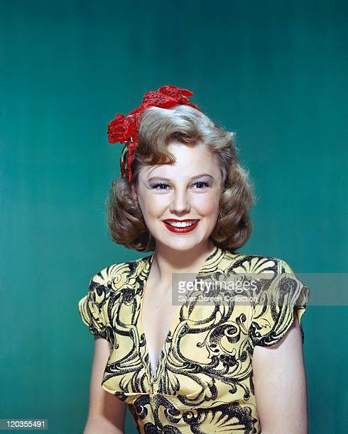 June Allyson US actress smiling wearing a yellowandblack shortsleeved top with red flowers in her hair in a studio portrait against a petrol blue...