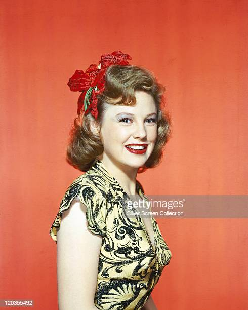 June Allyson US actress smiling wearing a yellowandblack shortsleeved top with red flowers in her hair in a studio portrait against a red background...