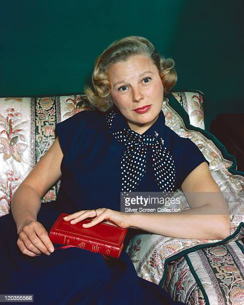 June Allyson US actress wearing a dark blue dress and a dark blue polka dot scarf around her neck holding a book by Edgar Allan Poe while sitting on...