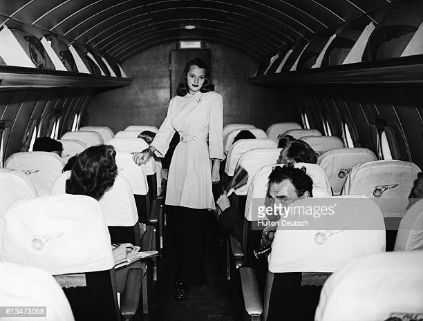 June Fogg models a blackandwhite lounge suit during a fashion show staged on board a Pan American Airways Clipper aeroplane during its transatlantic...