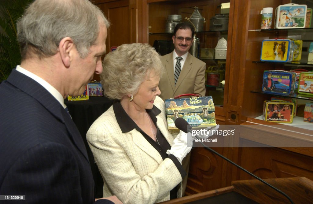 June Lockhart, of 'Lost in Space', presents the 'Lost in Space' lunchbox into the 'Taking America to Lunch' display with museum Director Dr. Brent D. Glass. NMAH, as David Shayt, curator of the lunchbox display looks on.