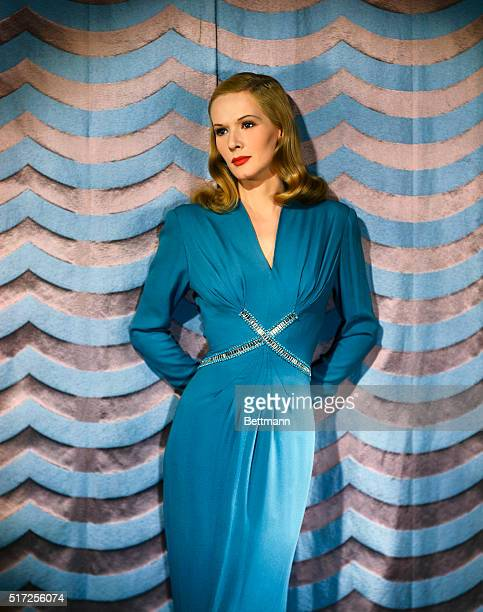 June Vincent, actress, wearing a full length dress that has a rhinestone and beaded applique in across the front of the torso.