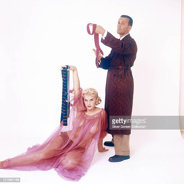 June Wilkinson British pinup girl reclining in a pink sheer fabric nightdress holding up a man's tie alongside a man wearing a dark red dressing gown...