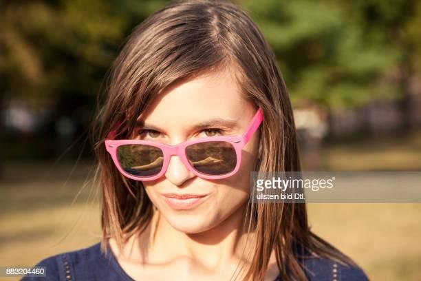 Jung attraktive Frau mit pinker Sonnenbrille