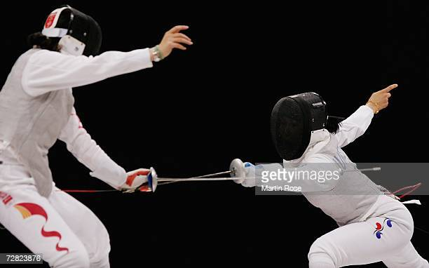 Jung Gil Ok of Republic of Korea competes with Chen Jinyan of China in the Women's Team Foil Gold Medal match during the 15th Asian Games Doha 2006...