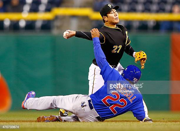 Jung Ho Kang of the Pittsburgh Pirates attempts to turn the double play over Addison Russell of the Chicago Cubs in the fifth inning during the game...