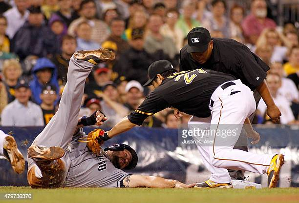 Jung Ho Kang of the Pittsburgh Pirates tags out Yonder Alonso of the San Diego Padres in a run down in the seventh inning during the game at PNC Park...