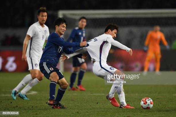 Jung Wooyoung of South Korea controls the ball under pressure of Yasuyuki Konno of Japan during the EAFF E1 Men's Football Championship between Japan...
