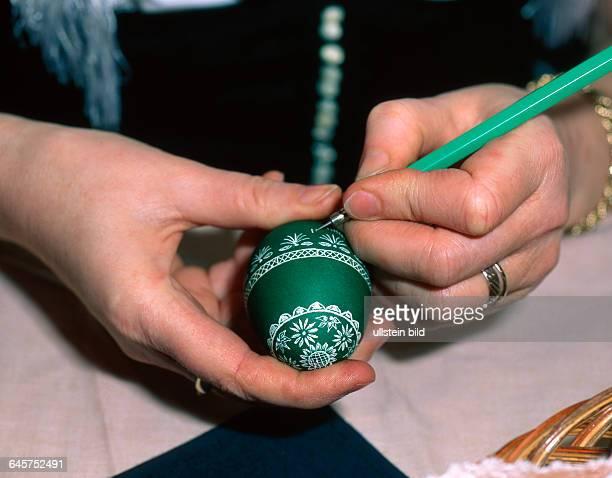 Junge Frau fertigt bunte sorbische Ostereier in Ritztechnik