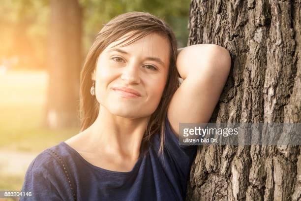 Junge Frau im Sommer an einem Baum lehnend